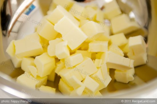 Cut the butter into small pieces and put into a large bowl.