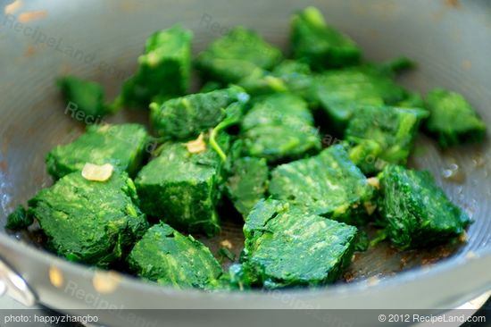Add the frozen spinach into the pan,