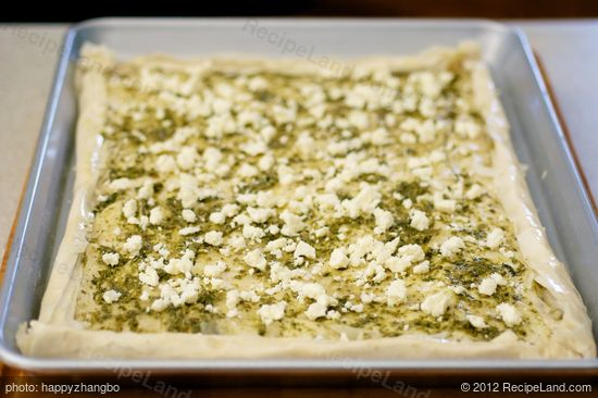 Sprinkle about half of the crumbled feta cheese over the pesto layer.