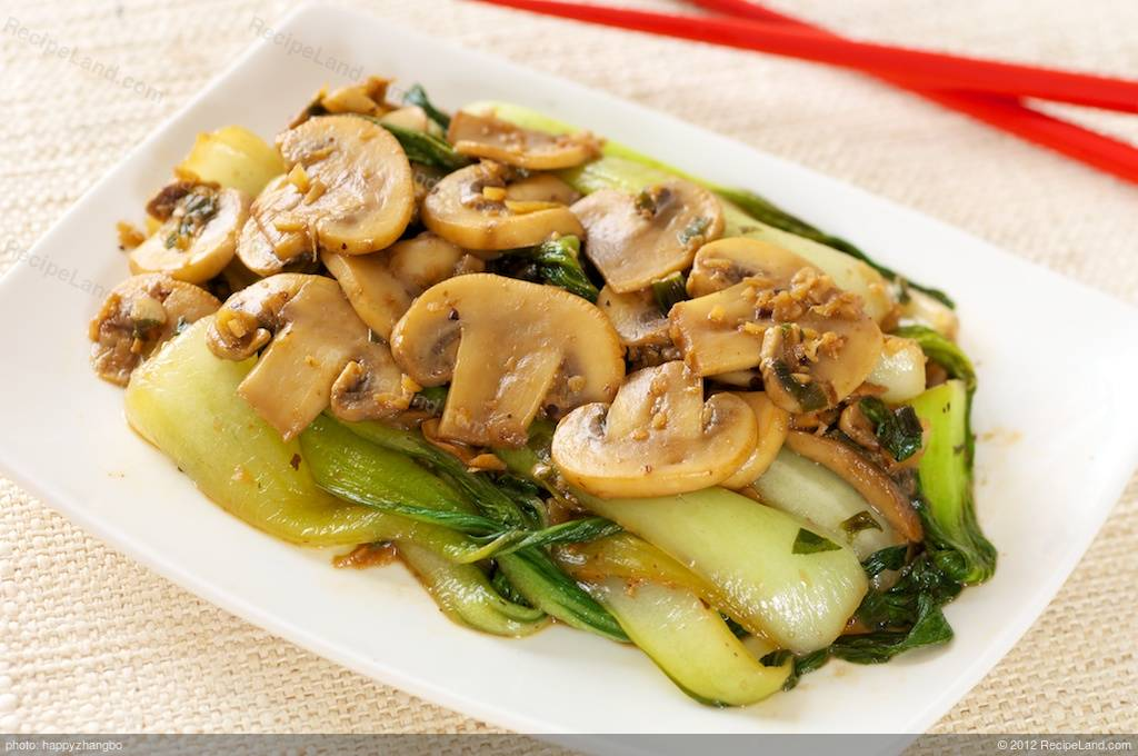 Quickly stir fry some bok choy and mushrooms with garlic, ginger and ...