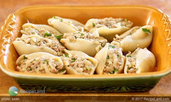 Pasta shells stuffed with beef in casserole dish, ready for the sauce