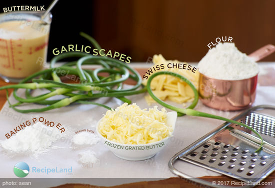 Ingredients to make garlic scape cheese biscuits on a wood cutting board