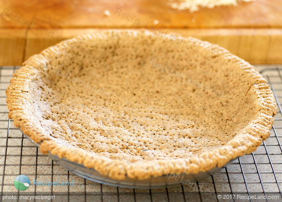 Blind baked herbed pie crust ready for filling in a glass pie plate on a wire rack.