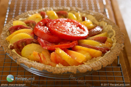 Fresh heirloom tomatoes (any good tomatoes work just as well) and herbs are baked on a bed of mozzarella cheese in a pie shell and topped with herbed garlic olive oil.