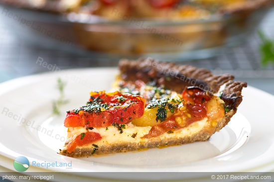 A juicy slice of Cheesy Herbed Fresh Heirloom Tomato Pie on a white plate with whole pie in the background and serving fork off to the side.