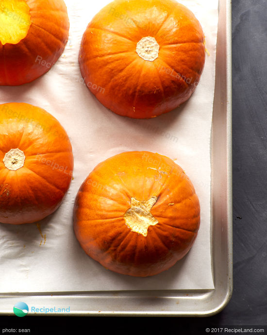 Halved sugar pumpkins, cut side down on a rimmed baking sheet lined with parchment paper.