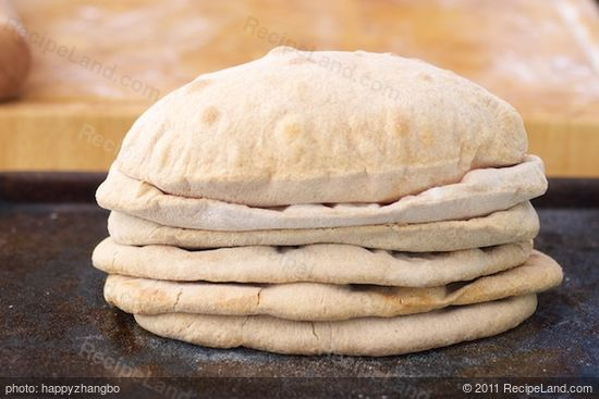 Stack baked naan bread together on a baking sheet...