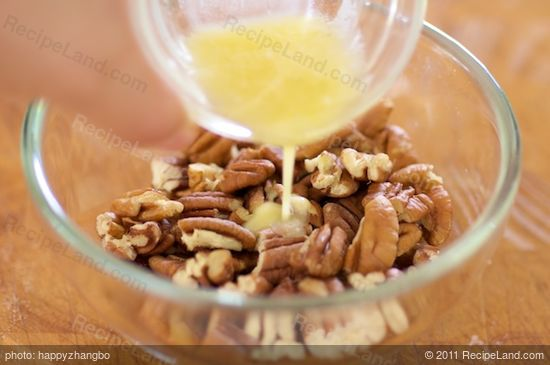 In a medium bowl, pour the melted butter into the coarsely chopped pecans.