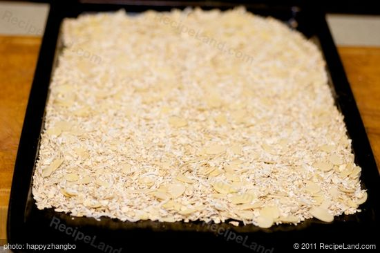 Place the oats, coconut, and almonds on a baking sheet, mix well and spread evenly.