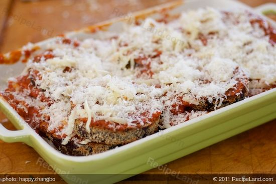 Lay another layer of eggplant slices, tomato sauce and two cheeses, repeat until all the ingredients have been used up.