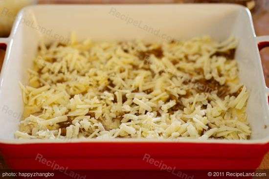 Spread half of the grated cheese over the onions.