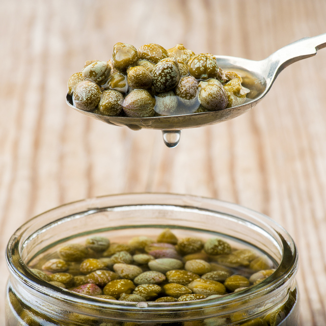 caper brine dripping from spoonful of capers